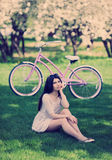 Молодая женщина в sundress наслаждаясь отключением велосипеда в парке Стоковое Изображение RF