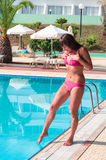 Молодая женщина в swimwear вздрагивает на касании ног холодной воды Стоковые Фотографии RF