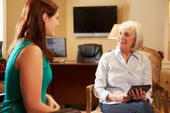 Молодая женщина говоря к консультанту используя таблетку цифров Стоковое Фото