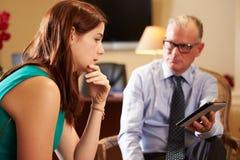 Молодая женщина говоря к мужскому консультанту используя таблетку цифров Стоковое фото RF