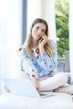 Молодая женщина говоря на мобильном телефоне и используя компьтер-книжку Стоковая Фотография RF