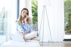 Молодая женщина говоря на мобильном телефоне и используя компьтер-книжку Стоковое Фото