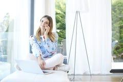 Молодая женщина говоря на мобильном телефоне и используя компьтер-книжку Стоковые Фото