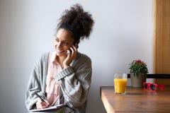 Молодая женщина говоря на мобильном телефоне и принимая примечания Стоковое Изображение RF