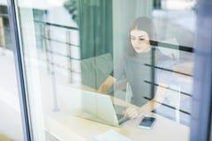 Молодая женщина говоря на телефоне и используя планшет через окно Стоковые Изображения RF