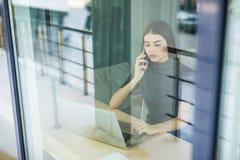 Молодая женщина говоря на телефоне и используя планшет через окно Стоковое Изображение RF