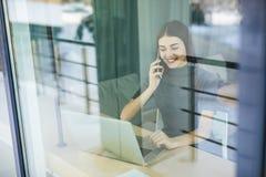 Молодая женщина говоря на телефоне и используя планшет через окно Стоковые Фотографии RF