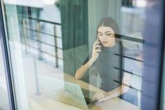 Молодая женщина говоря на телефоне и используя планшет через окно Стоковые Фото
