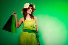 Молодая женщина девушки весны с зелеными хозяйственными сумками на зеленом цвете Стоковые Изображения