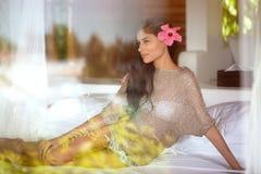 Молодая женщина лежа в кровати гостиничного номера стоковое фото