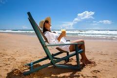 Молодая женщина лежа в соломенной шляпе в солнечных очках на пляже Стоковое Фото