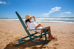 Молодая женщина лежа в соломенной шляпе в солнечных очках на пляже Стоковая Фотография RF