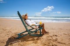 Молодая женщина лежа в соломенной шляпе в солнечных очках на пляже Стоковые Фотографии RF