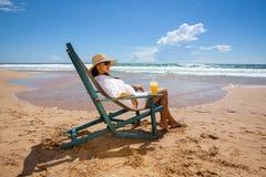Молодая женщина лежа в соломенной шляпе в солнечных очках на пляже Стоковое Изображение RF