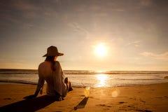 Молодая женщина лежа в соломенной шляпе в солнечных очках на пляже Стоковое Изображение