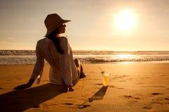 Молодая женщина лежа в соломенной шляпе в солнечных очках на пляже Стоковые Фото