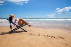 Молодая женщина лежа в соломенной шляпе на пляже Стоковое Фото