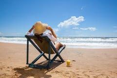 Молодая женщина лежа в соломенной шляпе на пляже Стоковая Фотография