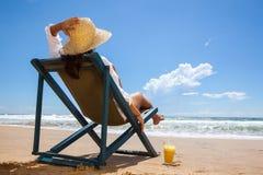 Молодая женщина лежа в соломенной шляпе на пляже Стоковые Фотографии RF