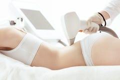 Молодая женщина лежа и получая заднюю часть заботы кожи лазера дальше Стоковые Фотографии RF