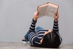 Молодая женщина лежа и читая книгу стоковые фотографии rf