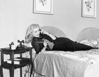 Молодая женщина лежа на ее кровати в спальне и говоря на телефоне (все показанные люди нет более длинные живущих и никакого estat Стоковые Изображения RF