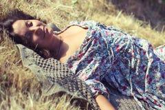 Молодая женщина лежа на желтой траве Стоковое Изображение