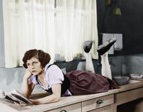 Молодая женщина лежа на счетчике кухни держа книгу и думать (все показанные люди нет более длинных никаких имущества exis живущих Стоковое Изображение