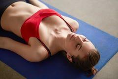 Молодая женщина лежа на циновке йоги с ей глаза закрыла Стоковые Изображения