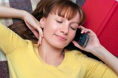 Молодая женщина лежа на шотландке с книгой и сотовым телефоном Стоковые Фото