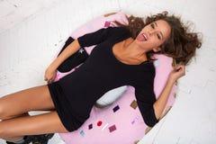 Молодая женщина лежит на донуте и язык показывать Белая не изолированная кирпичная стена, Стоковое Фото