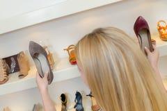 Молодая женщина держа 2 ботинка пар Стоковая Фотография