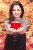 Молодая женщина держа большую красную чашку Стоковое Изображение