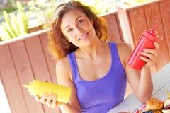 Молодая женщина держа бутылки соуса Стоковая Фотография RF