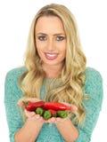 Молодая женщина держа горячие пряные красные и зеленые чили Стоковое Изображение