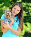 Молодая женщина держа ее сладостного маленького щенка - напольного портрета Стоковые Фото
