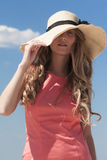 Молодая женщина держа ее шляпу с одной рукой Стоковое Фото