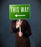 Молодая женщина держа знак направления Стоковая Фотография RF