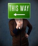 Молодая женщина держа знак направления Стоковые Фотографии RF