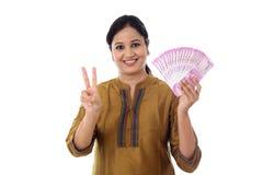 Молодая женщина держа индейца 2000 примечаний рупии и делая vic Стоковое фото RF