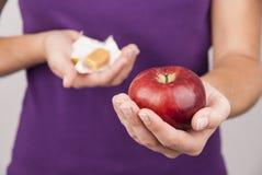 Молодая женщина держа конфету и яблоко Стоковые Фотографии RF