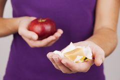 Молодая женщина держа конфету и яблоко Стоковые Изображения RF