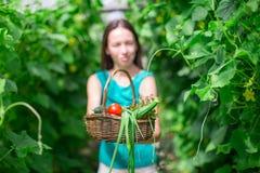 Молодая женщина держа корзину растительности и лука Стоковые Фото