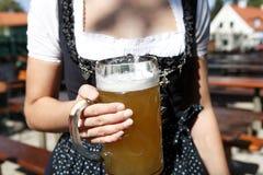 Молодая женщина держа кружку пива в саде пива стоковое фото
