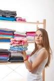 Молодая женщина держа кучу одежд Стоковое Изображение RF