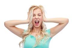 Молодая женщина держа к ее голове и кричащая стоковая фотография rf