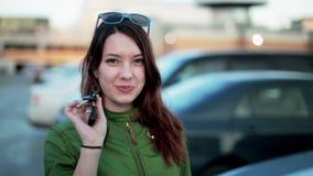 Молодая женщина держа ключи нового автомобиля и усмехаться