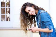 Молодая женщина держа мобильный телефон и усмехаться Стоковые Изображения