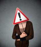 Молодая женщина держа дорожный знак возгласа Стоковая Фотография RF