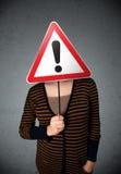 Молодая женщина держа дорожный знак возгласа Стоковая Фотография